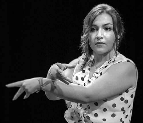 Gros plan sur le visage et les mains d'une danseuse flamenco
